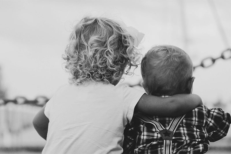 Brothers with back to camera - toddler with arm around baby's shoulders
