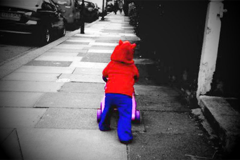 baby walking away with a pushcart