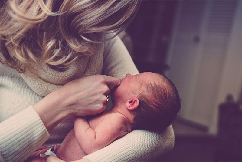 Newborn held by his mum