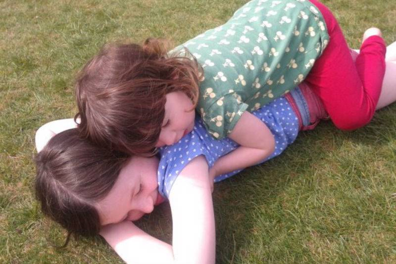 Daughters playing in the sunshine on the grass