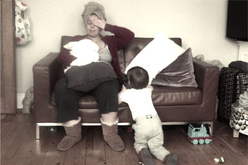 Mum of two - holding baby in her arms on the sofa while toddler hits her with a cushion