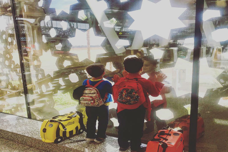 Children with suitcases at an airport.